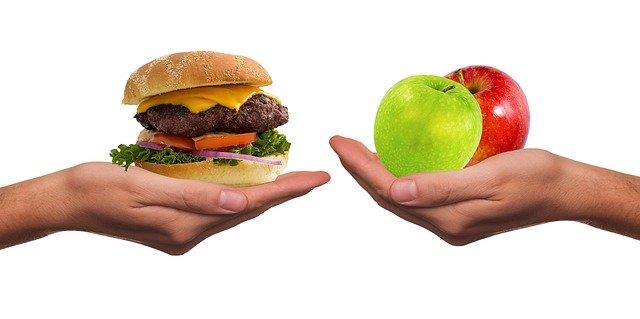 гамбургер в руке против яблок в руке
